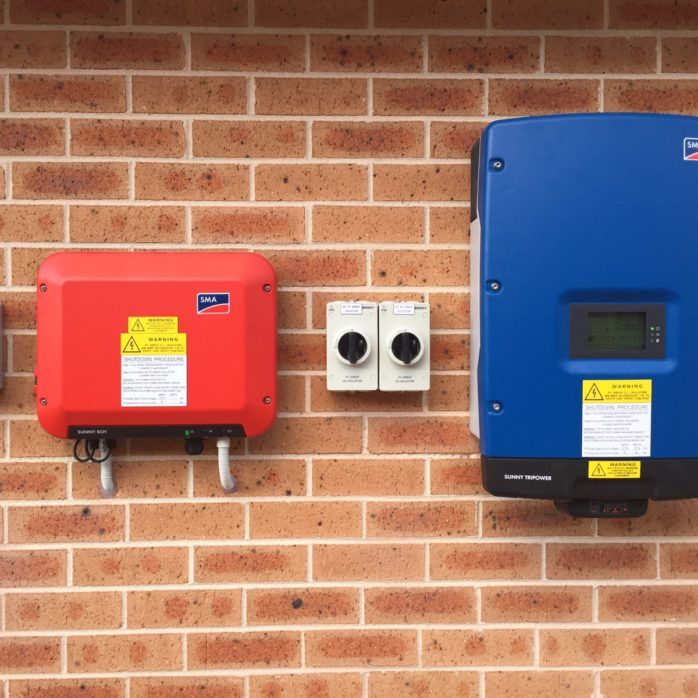 Red and Blue SMA inverters attached to a brick wall