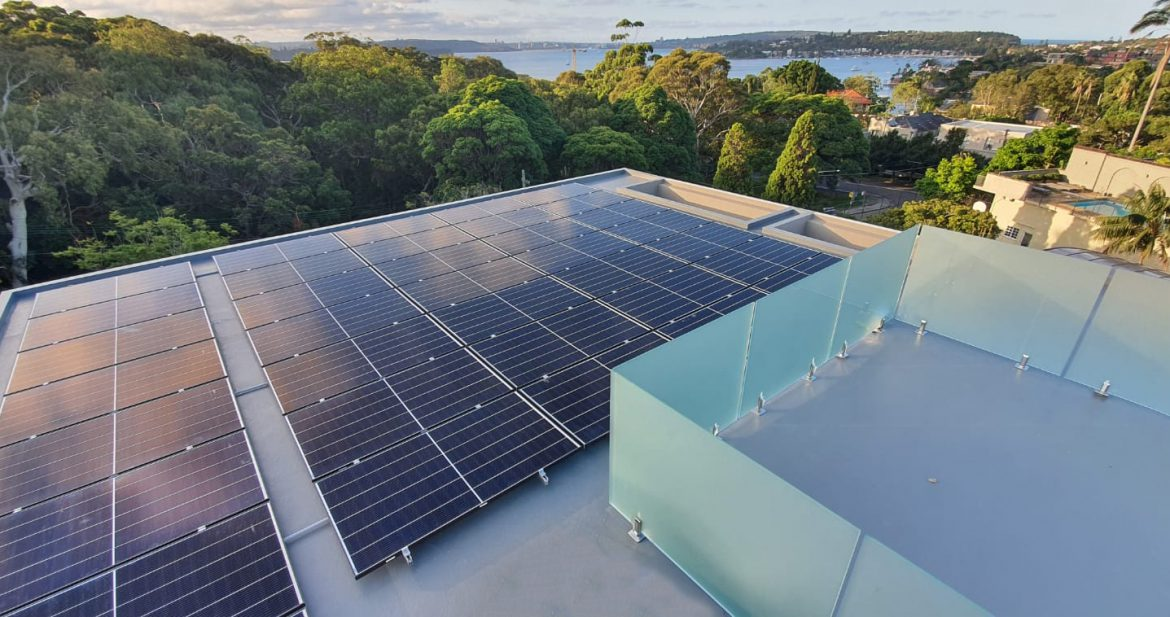 Top view of solar panel installed on the building surrounded by trees and a lake